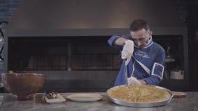 De mens in blauwe chef-kok eenvormige scherpe smakelijke gekookte zoete oostelijke pastei kunaf bestrooide met pistaches in reepj stock videobeelden