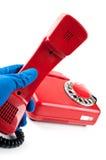 De mens in blauwe handschoenen raapte het op de rode telefoon Stock Foto