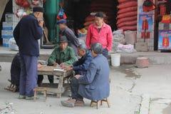 De mens in blauwe Mao-kostuums is speelkaarten in China Stock Foto's