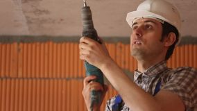 De mens boort plafond stock video