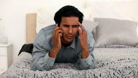 De mens is boos op zijn celtelefoon op het bed stock video