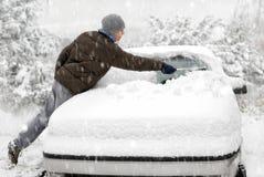 De mens borstelt sneeuw van zijn auto Stock Afbeelding