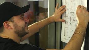 De mens, bouwer onderzoekt zorgvuldig en trekt iets op plan van de flat stock videobeelden
