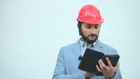 De mens in bouwhelm maakt berekeningen stock videobeelden