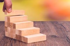 De mens bouwt een houten ladder Concept: stabiele ontwikkeling royalty-vrije stock fotografie
