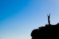 De mens bovenop de berg bereikt voor de glorie Stock Foto's