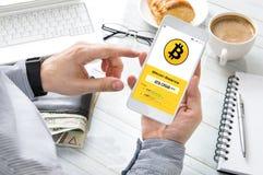 De mens controleert bitcoin tarief bij zijn cryptocurrencyportefeuille royalty-vrije stock afbeelding