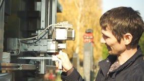 De mens controleert de nauwkeurigheid van de installatie van de gravuremachine stock footage