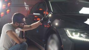 De mens controleert resultaat van het oppoetsen van auto met een flitslicht stock footage
