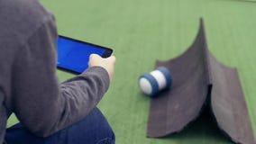 De mens controleert de robot gebruikend de tablet Moderne robot bij de tentoonstelling van nieuwe technologieën stock video