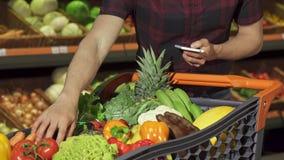 De mens controleert zijn het winkelen lijst op smartphone stock videobeelden