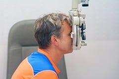 De mens controleert zijn visie op de machine stock afbeelding