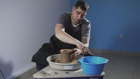 De mens creeert zacht kruik van klei De pottenbakker creeert product op het wiel van de pottenbakker stock footage