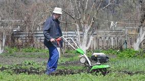 De mens cultiveert de grond in de tuin met een uitloper, die de grond voor het zaaien voorbereiden stock video