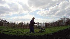 De mens cultiveert de grond in de tuin met een uitloper, die de grond voor het zaaien voorbereiden stock videobeelden