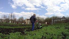 De mens cultiveert de grond in de tuin met een uitloper, die de grond voor het zaaien voorbereiden stock footage