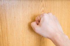 De mens (de bezoeker) klopt op gesloten houten deur stock afbeeldingen