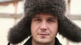 De mens in de hoed van het de winterbont onderzoekt de camera stock footage