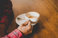 De mens in de koffie met koffiekop ontspant binnen tijd Stock Foto's