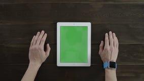 De mens die aan een tabletpc werken met greenscreen stock footage