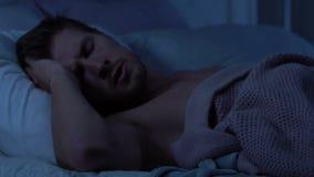 De mens die die aan slaap proberen, door straatlawaai of luide buur wordt gestoord spreekt, slapeloosheid stock video