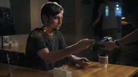 De mens die betaling verrichten door NFC-technologie op mobiele telefoon in koffie, student betaalt koffierestaurant stock video