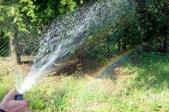 De mens die de binnenplaats water geven creeert een kunstmatige regenboog stock fotografie