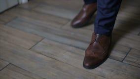De mens die broeken en bruine leerschoenen dragen loopt binnen Volgend schot van man leerschoenen, close-upmening stock videobeelden