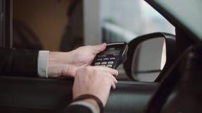 De mens die creditcard betalen voor het kopen van binnenauto, gaat een SPELDcode in Close-upmening van zakenmanhand van het autor stock video