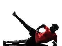 De mens die de voeten van de geschiktheidstraining omhoog uitoefenen silhouetteert Royalty-vrije Stock Foto