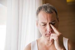 De mens die door venster kijken die ongerust gemaakt, drukte, nadenkende en eenzame lijdende depressie in het werkdruk kijken in Stock Afbeeldingen