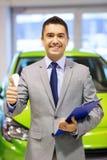 De mens die duimen tonen bij auto verschijnt of autosalon Stock Afbeeldingen