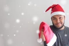 De mens die een Kerstmanhoed dragen geeft Kerstmanhoed voor u stock foto