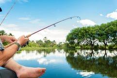 De mens die een vis met de staaf vangen enverged, houdend een staaf met zijn handen op een meer met een mooie rond aard Royalty-vrije Stock Afbeeldingen