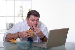 De mens die en eet unhealt voedsel werkt Stock Foto