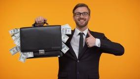 De mens die geval tonen pakte met geld in, duim-omhoog knipogend en doend, lening, krediet stock video
