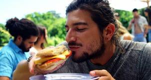 De mens die hamburger eten bij in openlucht roostert partij stock video
