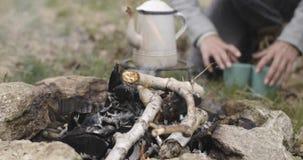 De mens die hout wegschoppen opent brandplaats dichtbij het kamperen tentplaats het programma terwijl vrouw die hete drank voorbe stock footage