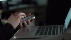 De mens die laptop telefoonaantal bekijken en draait het dan op een smartphone stock footage