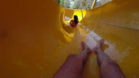 De mens die onderaan gekleurde waterdia gaan en loopt meisje vooraan met plons van water in waterpark de achterstand in op weeken stock videobeelden