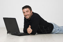 De mens die op vloer met laptop ligt en geeft duimen Royalty-vrije Stock Afbeeldingen