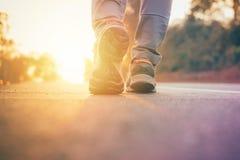 De mens die op weg met zon lichte gloed lopen, sluit omhoog op de trainingwellness van de schoenjogging na het werk stock afbeelding