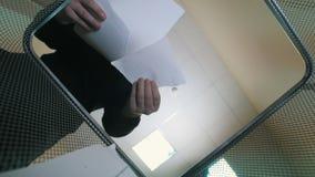 De mens die pices van document in afval werpen kan bak - bodemmening stock footage