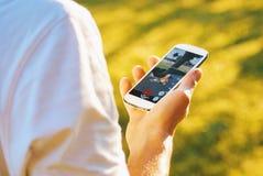 De mens die Pokemon spelen gaat spel op smartphone bij natuurlijk omgeeft Stock Foto's