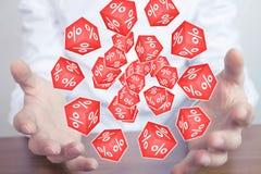 De mens die rode kubussen met een percent houden ondertekent Stock Fotografie