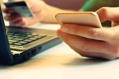De mens die smartphone met creditcard gebruiken betaalt door creditcard en overlapping Stock Foto