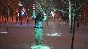 De mens die sneeuwvlok vangen dient nachtpark in stock footage
