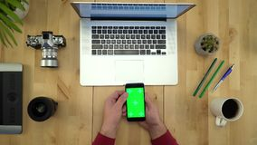 De mens die Telefoon met het Groene Scherm met behulp van, die bij Lijstvlakte werken lag stock video