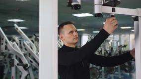 De mens die tricep bewerkt alvorens wapenstraining in gymnastiek te doen aanpassen machinaal stock video