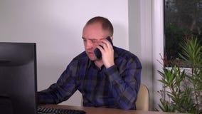 De mens die van de ambtenarenbediende telefoneert en met computer bij zijn bureau in bureau werken spreken stock footage